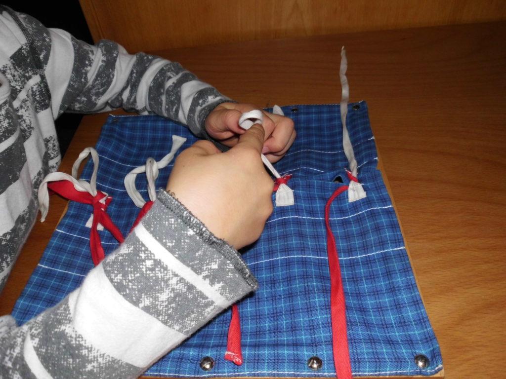 Das Bild zeigt die Hände und Arme eines Kindes auf einem Tisch. Die Hände liegen auf einem Stück Stoff, auf dem Schnüre befestigt sind. Das Kind übt Schleifen zu machen. Das Stück Stoff ist ein Übungsmaterial.