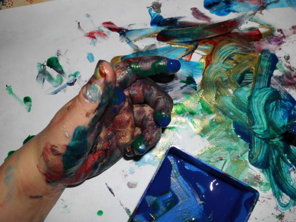 Das Bild zeigt eine Kinderhand auf einem mit Papier ausgelegtem Tisch. Die Hand ist mit Fingerfarbe bedeckt. Auf dem Papier wurde schon mit der Fingerfarbe gemalt. Das Bild ist sehr bunt.